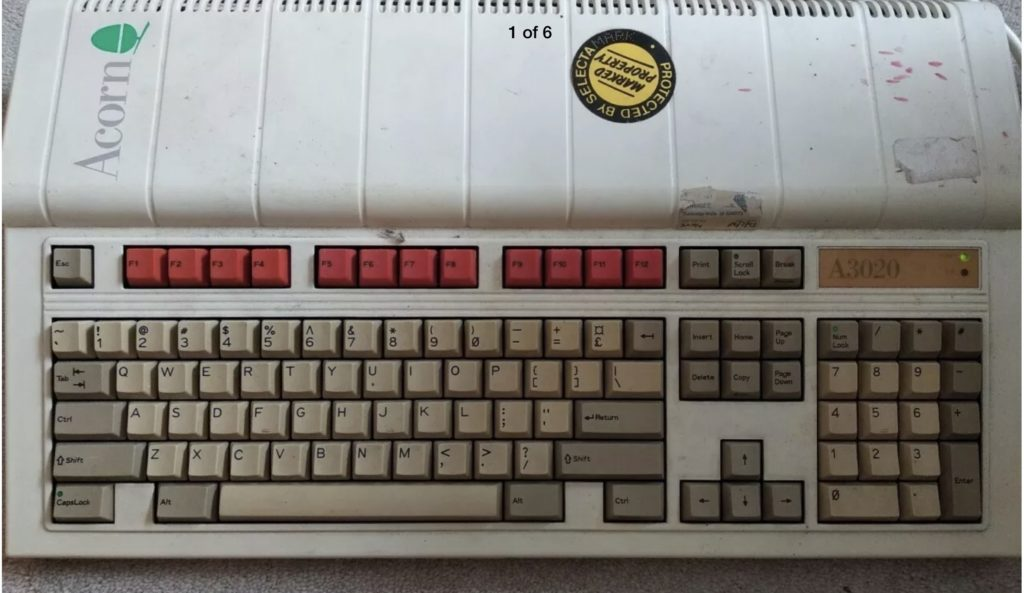 An Acorn Archimedes A3020 covered in dirt, stickers, etc.